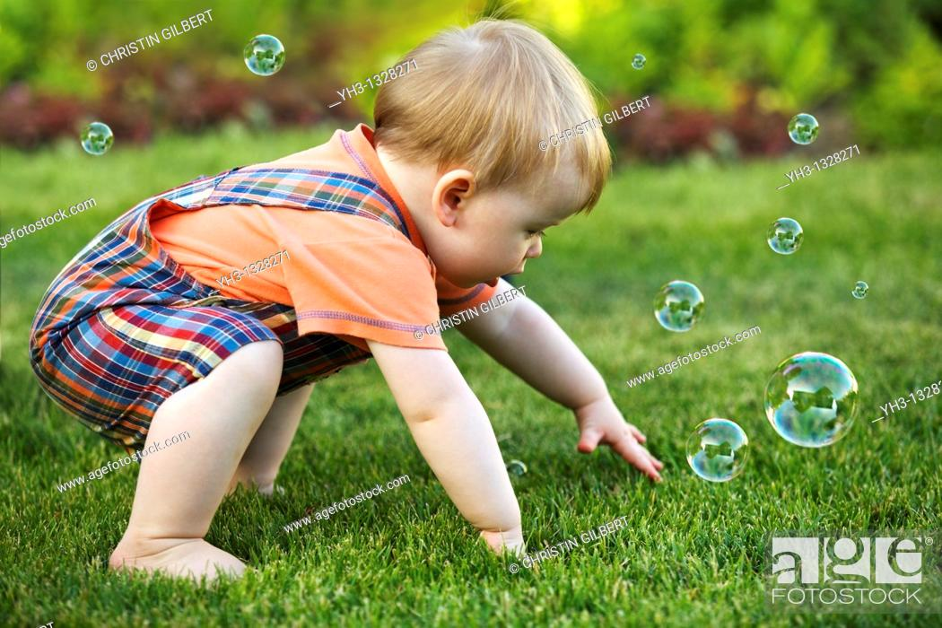 Stock Photo: Portrait of a toddler playing with bubbles in the garden.