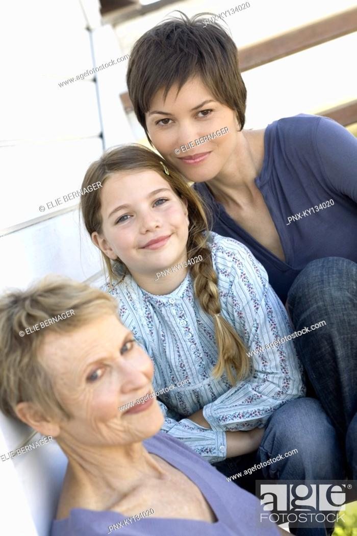 Stock Photo: Female members of three generation family looking at camera, outdoors.