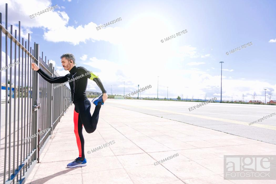 Stock Photo: young adult man stretching on the outdoors before to run.