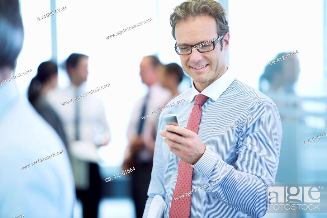 Stock Photo: Businessman using cell phone in office.