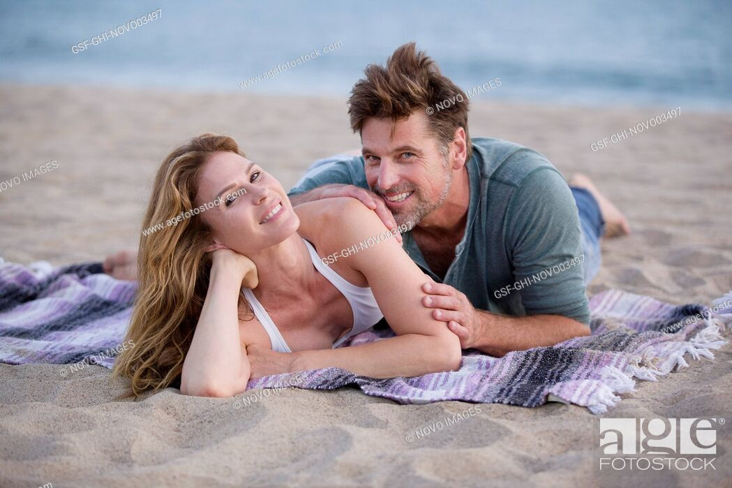 Imagen: Smiling Mid-Adult Couple Laying on Blanket at Beach.