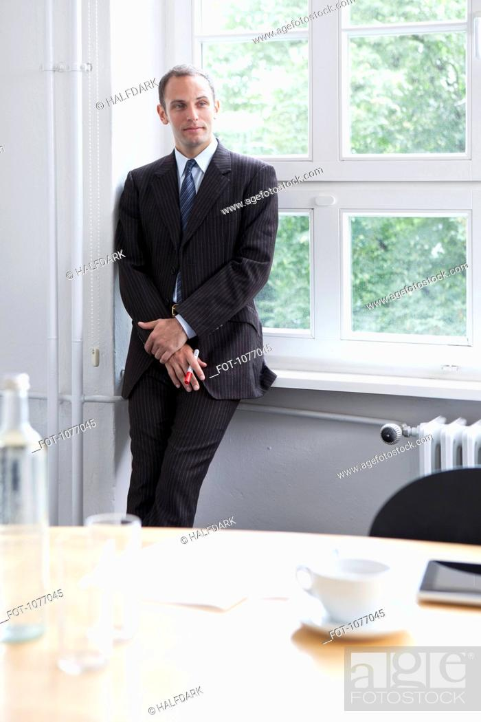 Stock Photo: A businessman leaning against a window sill in a conference room.