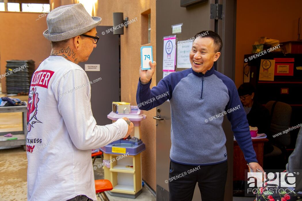 Stock Photo: A Vietnamese-American priest verifies a client's membership number at the charity food pantry of a Southern California Catholic church.