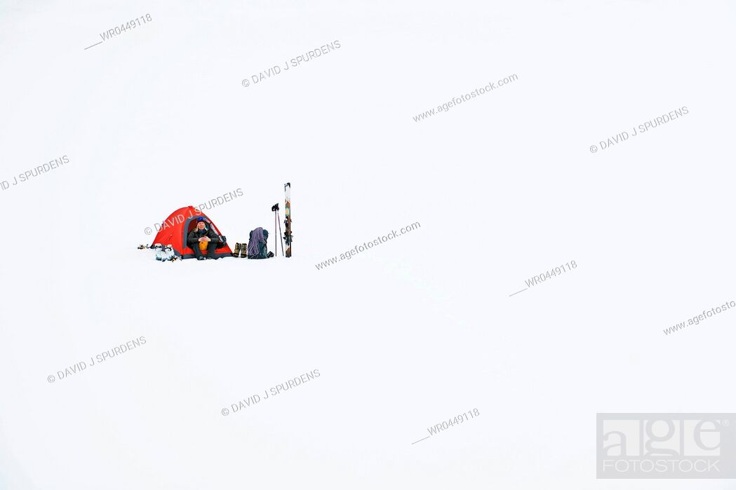 Stock Photo: A mountaineer ski tourer sitting in her tent.