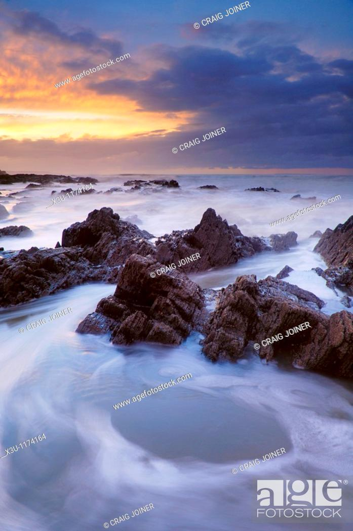 Stock Photo: The incoming tide washing over the rocks at dusk at Westward Ho! in Devon, England.