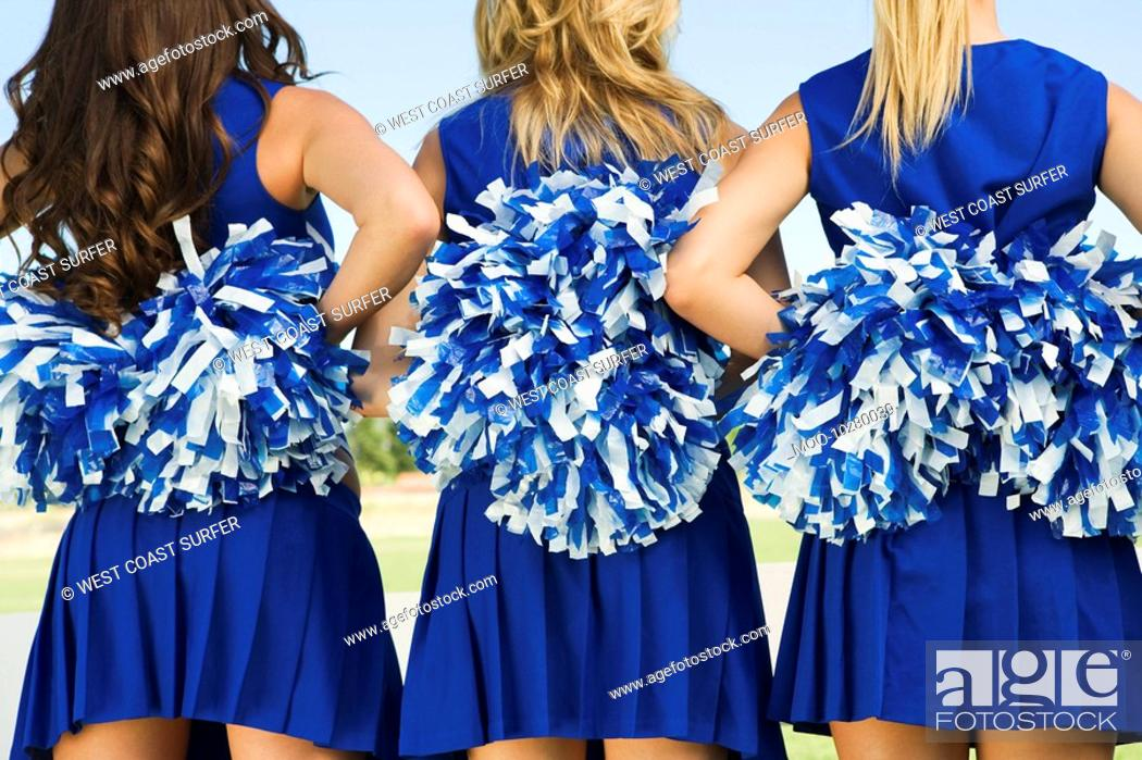 Stock Photo: Cheerleaders holding pom-poms rear view mid section close-up.