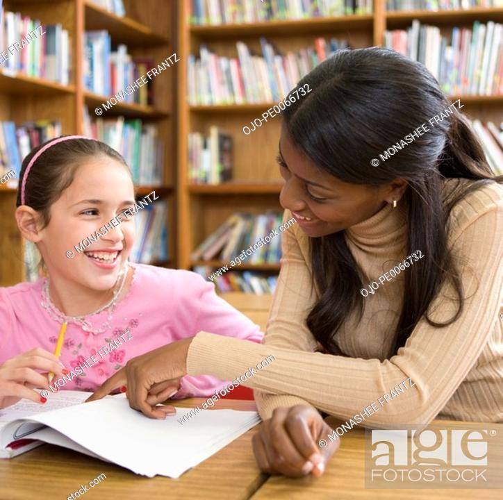 Stock Photo: Teacher helping girl with homework.