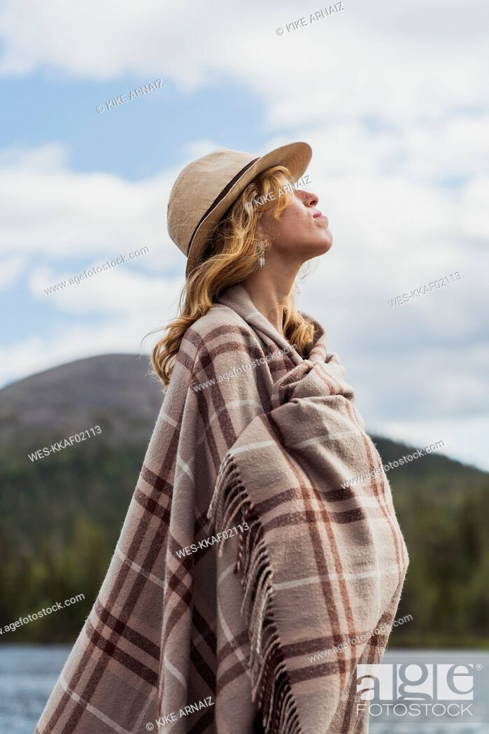 Stock Photo: Finland, Lapland, woman wearing a hat wrapped in a blanket standing at the lakeside.
