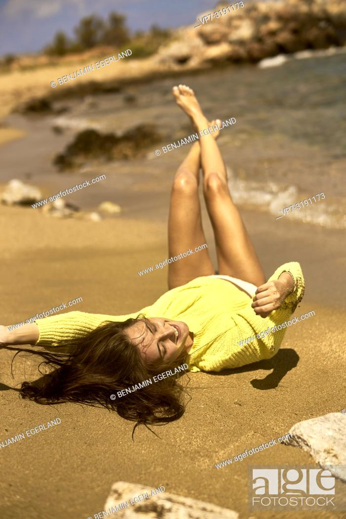 Stock Photo: Portrait of woman at the beach, wearing a yellow sweater. Crete, Greece.