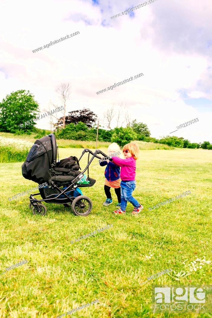 Stock Photo: Girls playing with baby carriage on grassy field against cloudy sky.