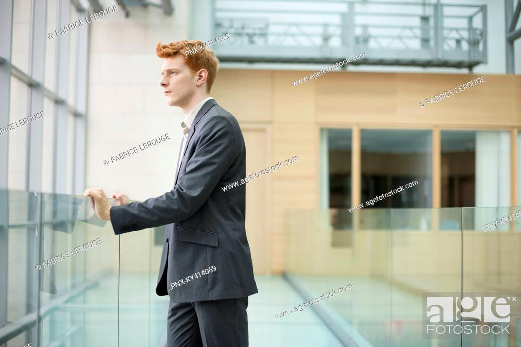 Stock Photo: Businessman looking through glass window in a corridor.