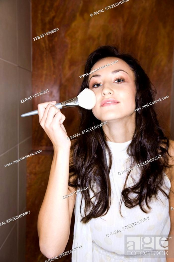 Stock Photo: young woman applying rouge on face.