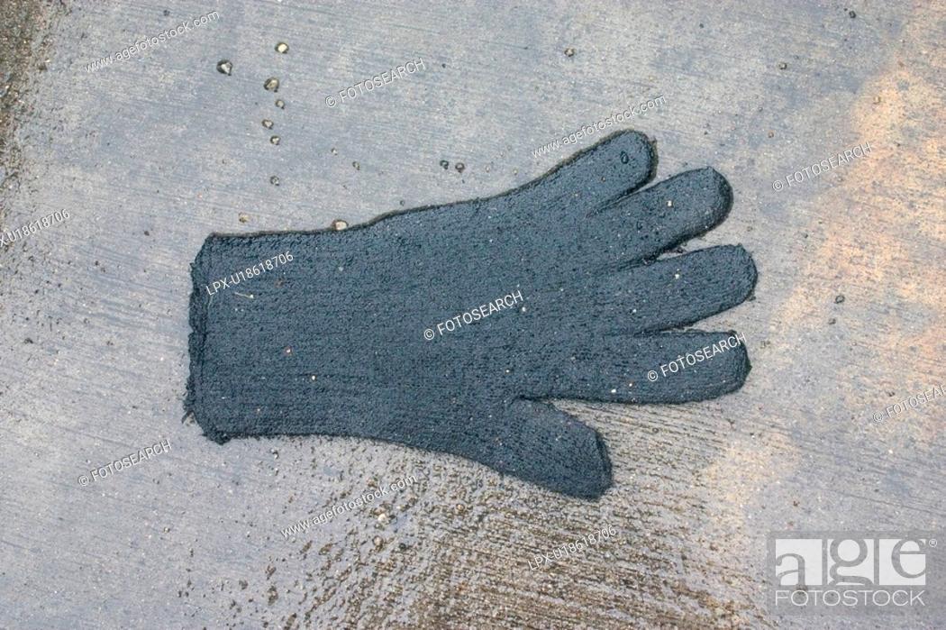 Stock Photo: Lost glove on wet sidewalk.