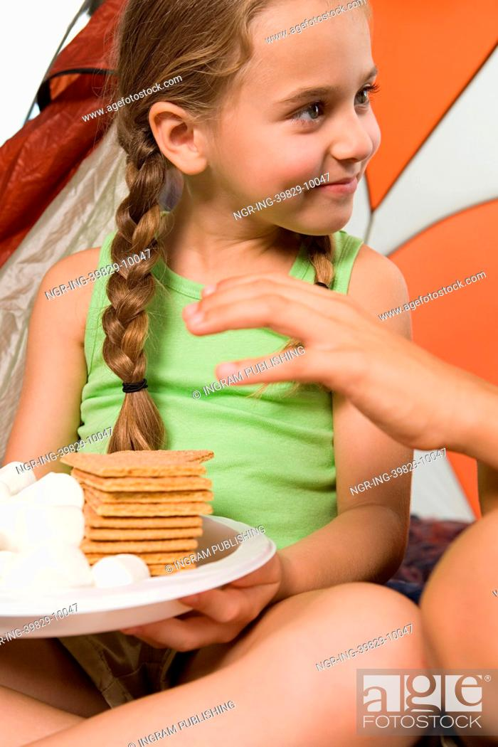 Photo de stock: Child reaching for plate of treats.