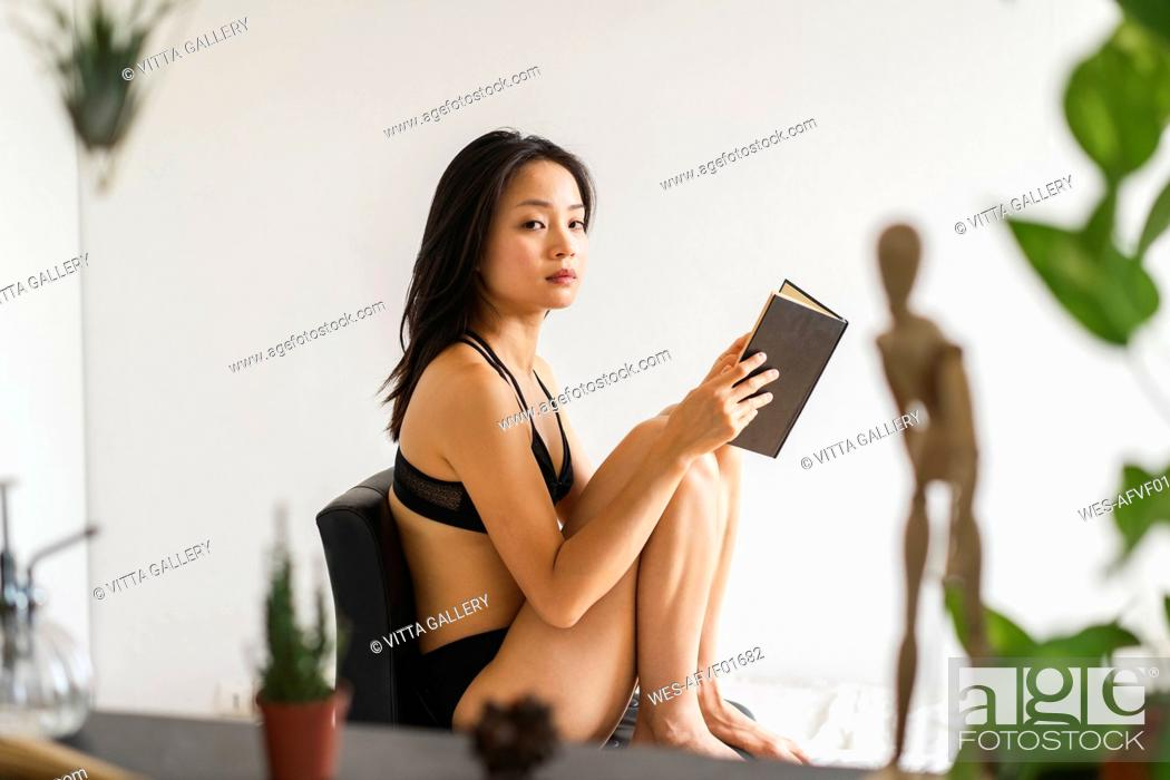 Stock Photo: Portrait of attractive young woman in lingerie sitting on chair at home reading book.