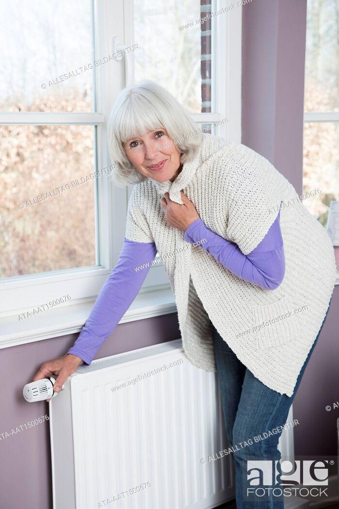 Stock Photo: Freezing woman turning the heating up.