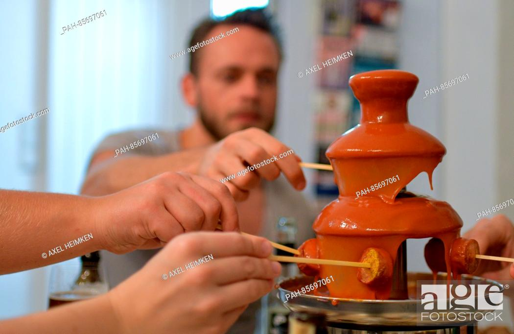 Stock Photo: Guests at the restaurant 'Pop Up Store' dip pieces of sausage into a fountain of curry sauce in Hamburg, Germany, 15 November 2016.