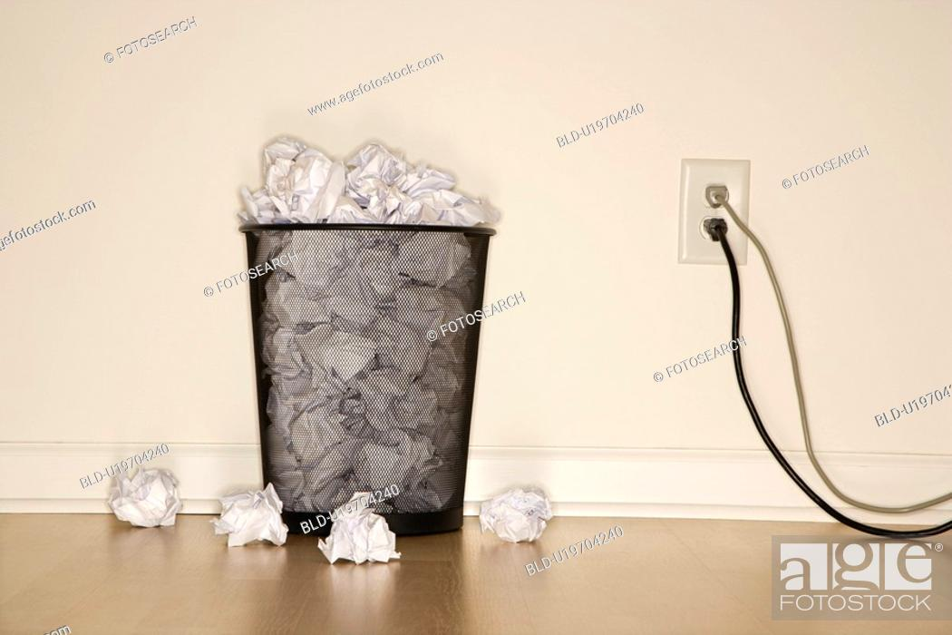 Stock Photo: Full wire mesh trash can with crumpled paper next to electrical outlet and plugs.