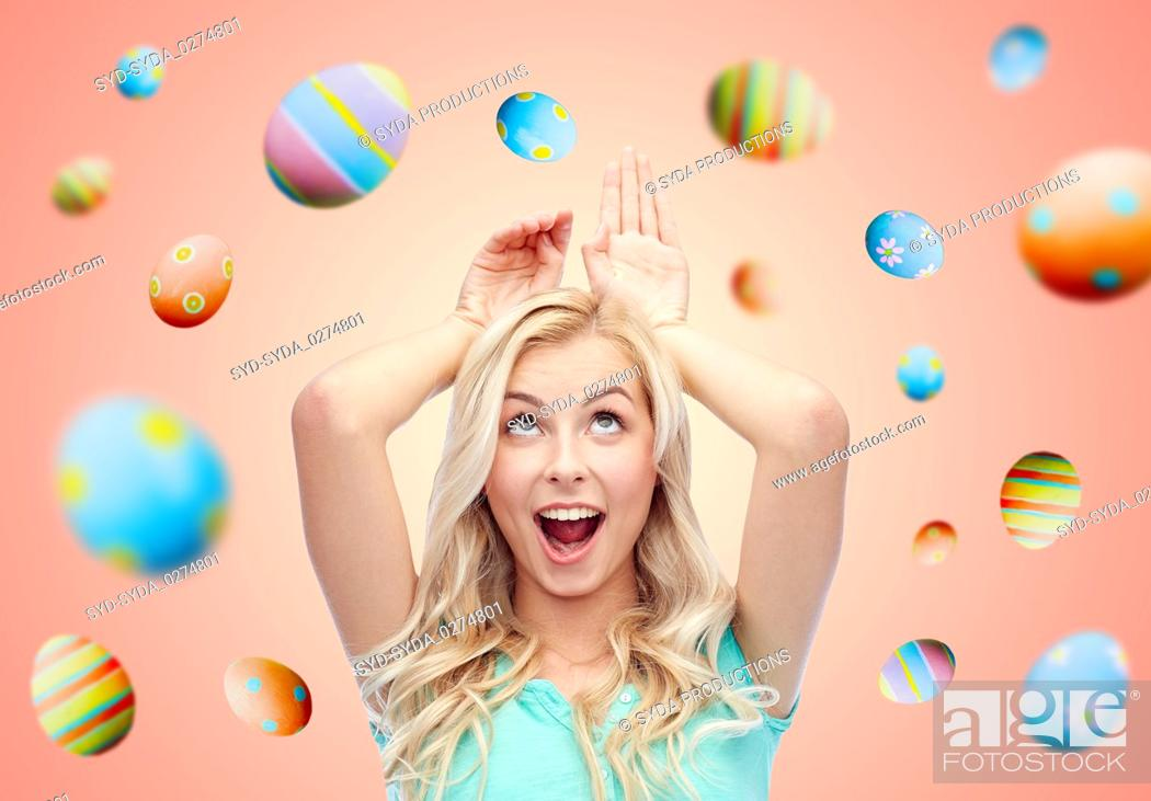 Stock Photo: happy smiling young woman making easter bunny ears.