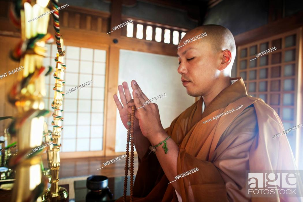 Stock Photo: Side view of Buddhist monk with shaved head wearing golden robe kneeling indoors in a temple, holding mala, eyes closed.