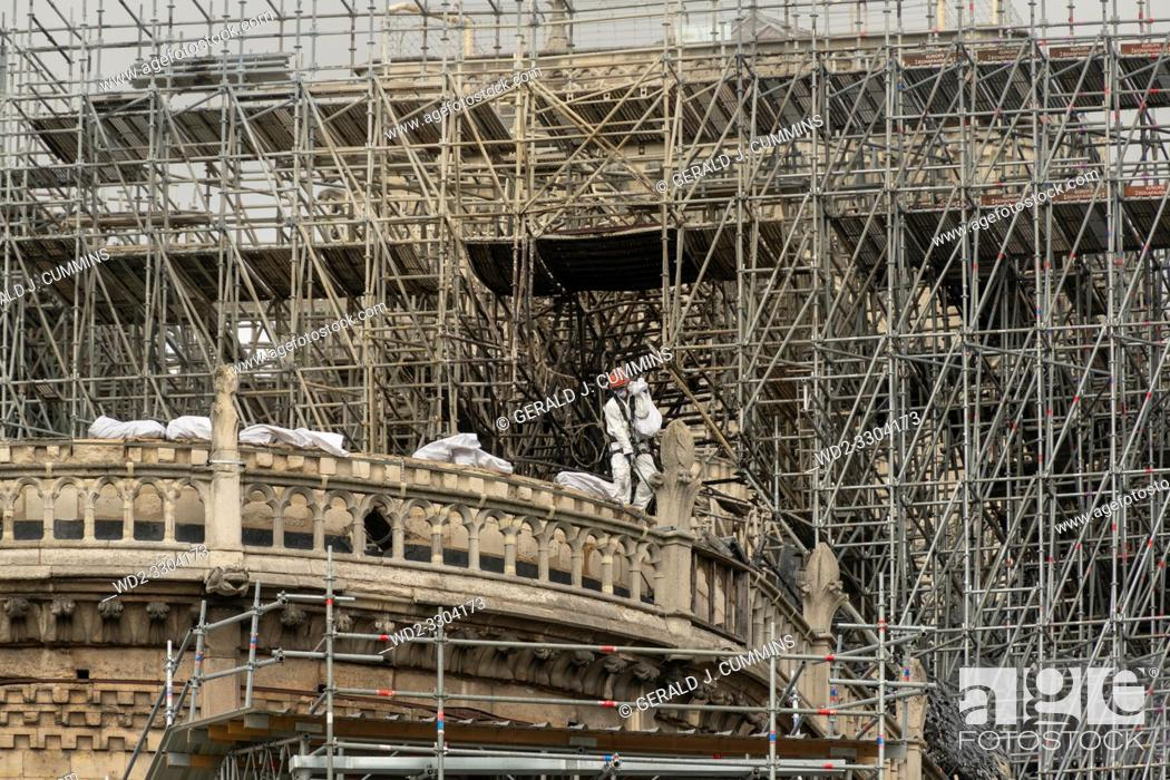Stock Photo: PARIS, FRANCE - 19 APRIL 2019 Notre Dame cathedral, a man removes charred timber from the roof. The remains of the melted scaffolding behind him is witness to.