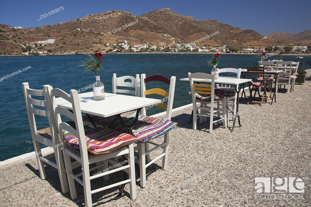 Photo de stock: Tables and chairs of a traditional restaurant by the sea near the port, Ios Island, Cyclades Islands, Greek Islands, Greece, Europe.