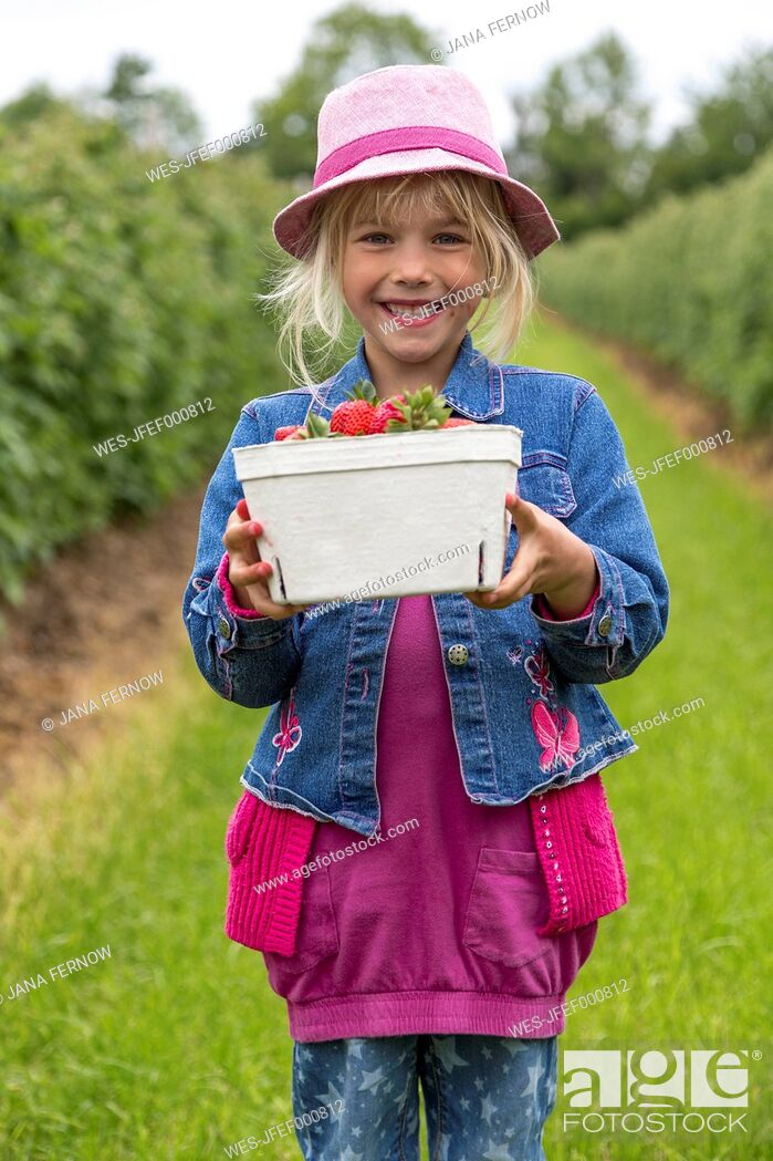 Stock Photo: Portrait of happy little girl holding box of strawberries on strawberry field.