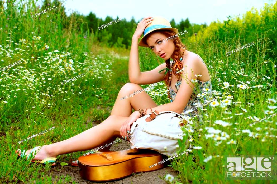 Stock Photo: Beautiful romantic girl with a guitar on a country road on a sunny summer day.