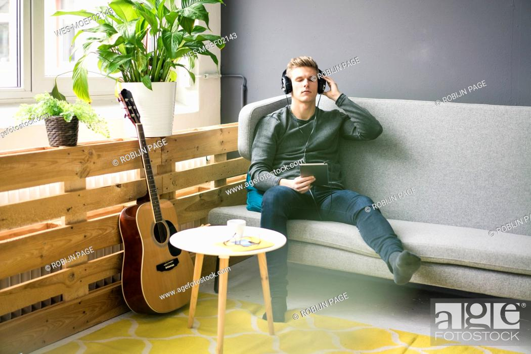Imagen: Relaxed young man with tablet and guitar listening to music with headphones.