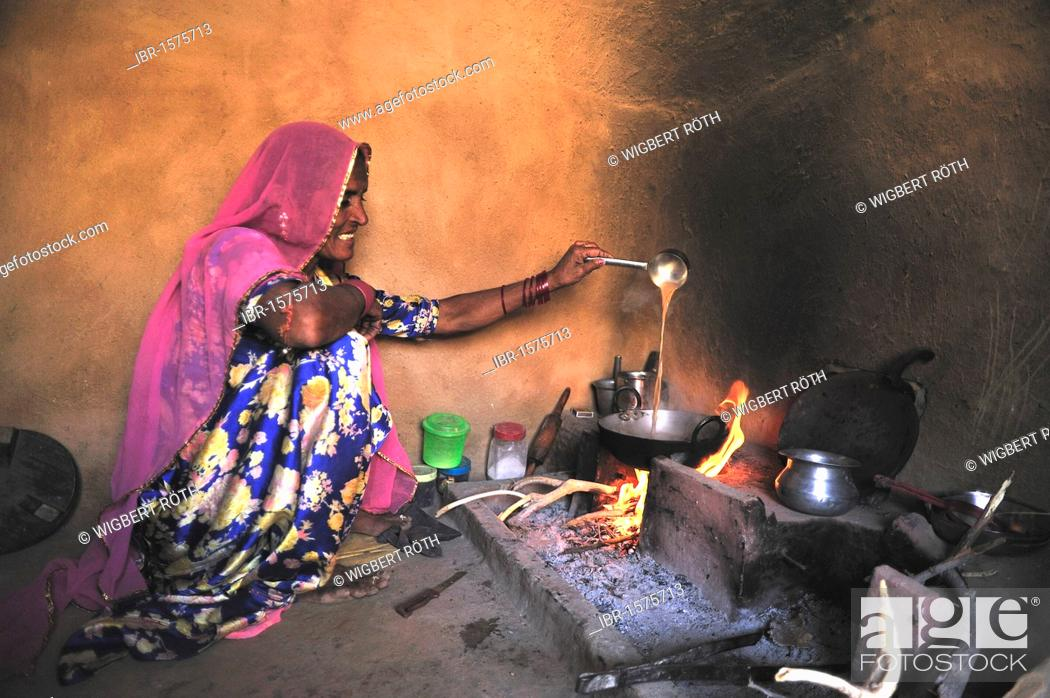 Stock Photo: Woman preparing the traditional milk tea with ginger on an open hearth fire, Thar Desert, Rajasthan, India, Asia.