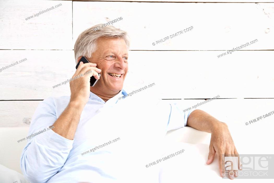 Stock Photo: Spain, Senior man talking on mobile, smiling.