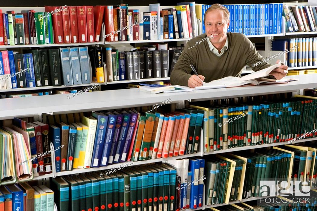 Stock Photo: Man studying in library, smiling, portrait.