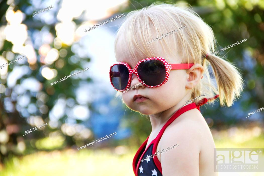 Stock Photo: A one year old toddler wearing bright red sunglasses on Independence Day in Liberty Lake, Washington, USA.