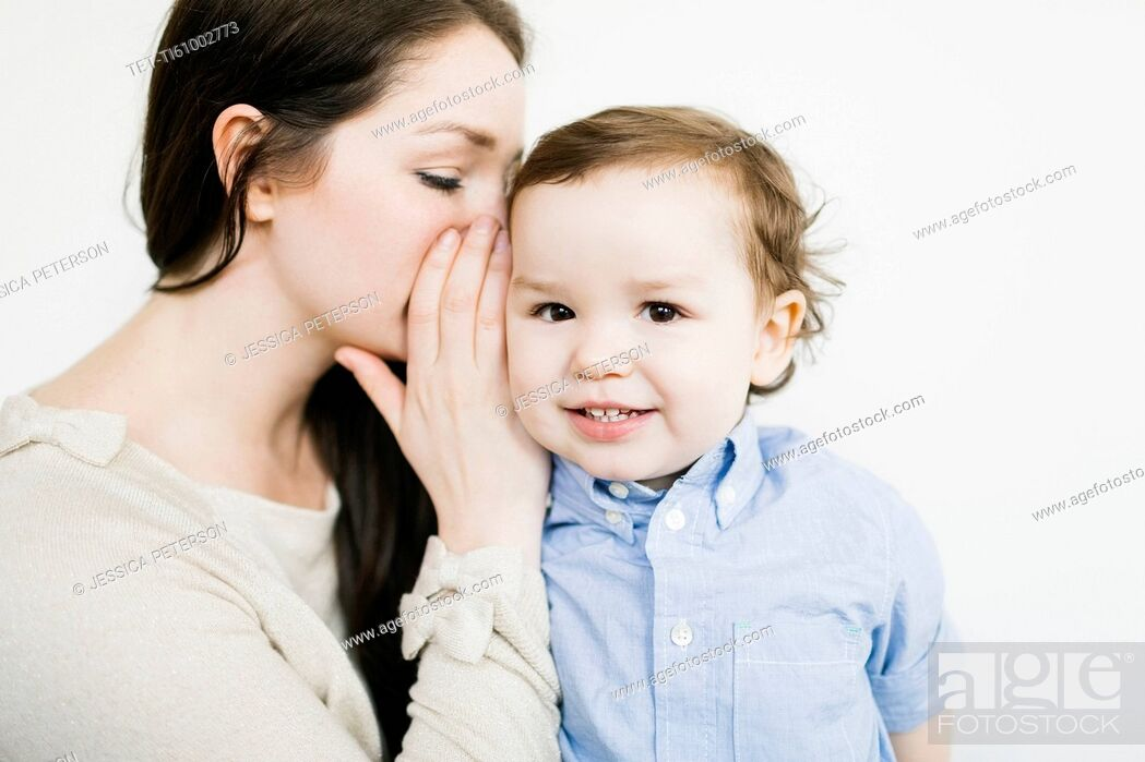 Stock Photo: Mother whispering into son's (4-5) ear.