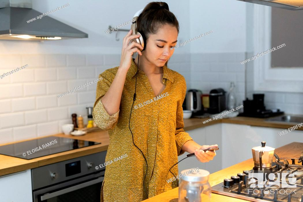 Stock Photo: Young woman listening musuc in the kitchen, while preparing her morning coffee.