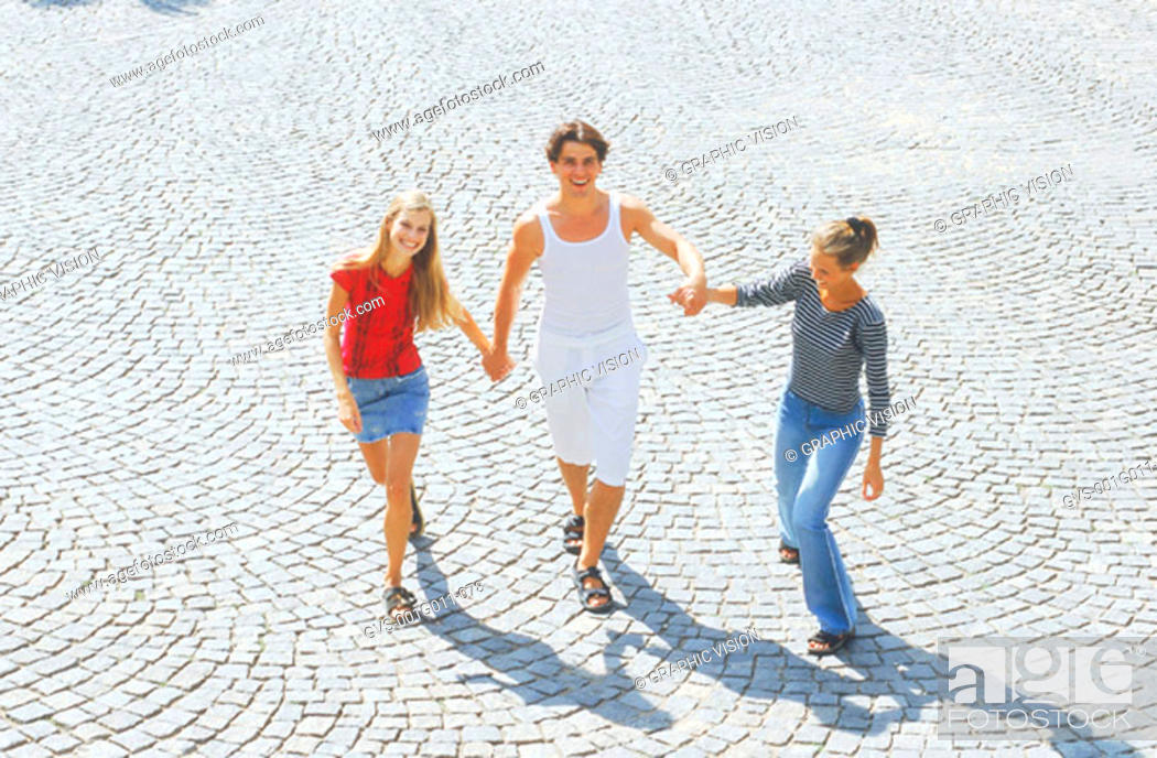 Stock Photo: Portrait of a young man and two young women walking holding hands.