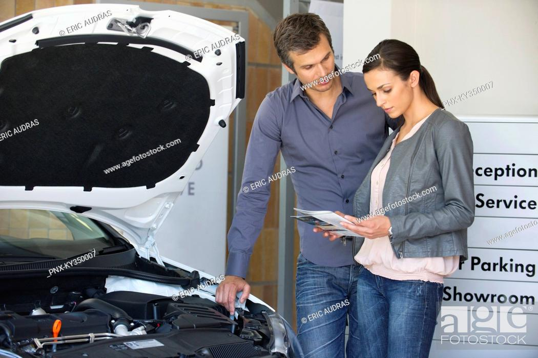Stock Photo: Couple looking at a car catalog in showroom.