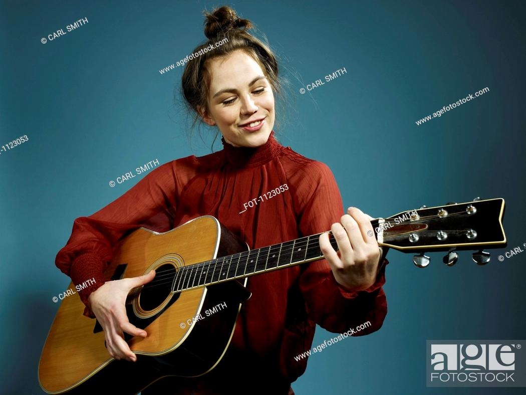 Stock Photo: A young woman playing an acoustic guitar.