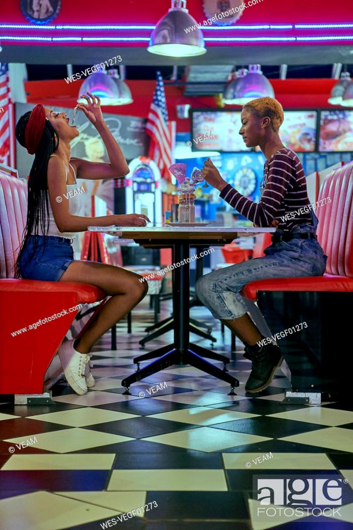 Stock Photo: Two woman sharing a milkshake on an american restaurant's table.