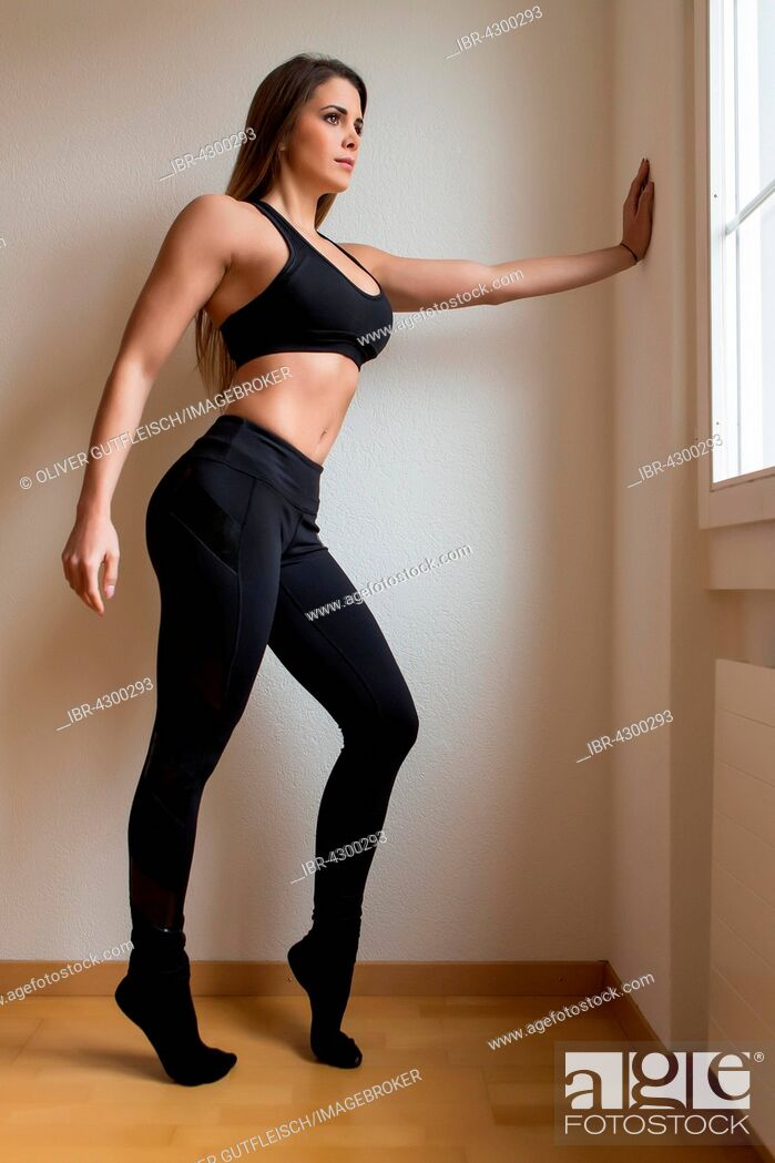 Stock Photo: Young woman in a black fitness sports outfit.