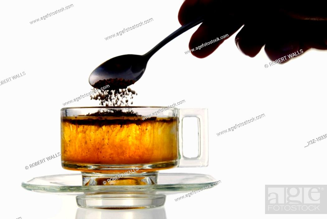 Stock Photo: Instant coffee added to water in a glass cup.