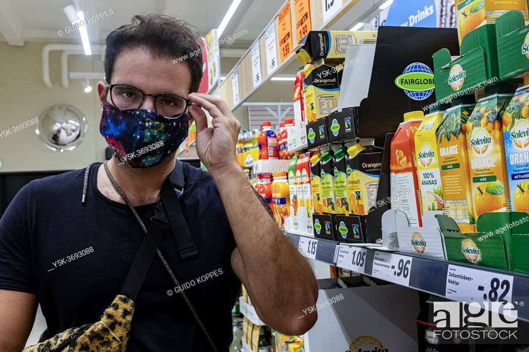 Stock Photo: Berlin, Germany. Mature gay male shopping for groceries inside a local supermarket wearing a 'protective' facemask due to Corona Outbreak and Covid-19 Crisis.