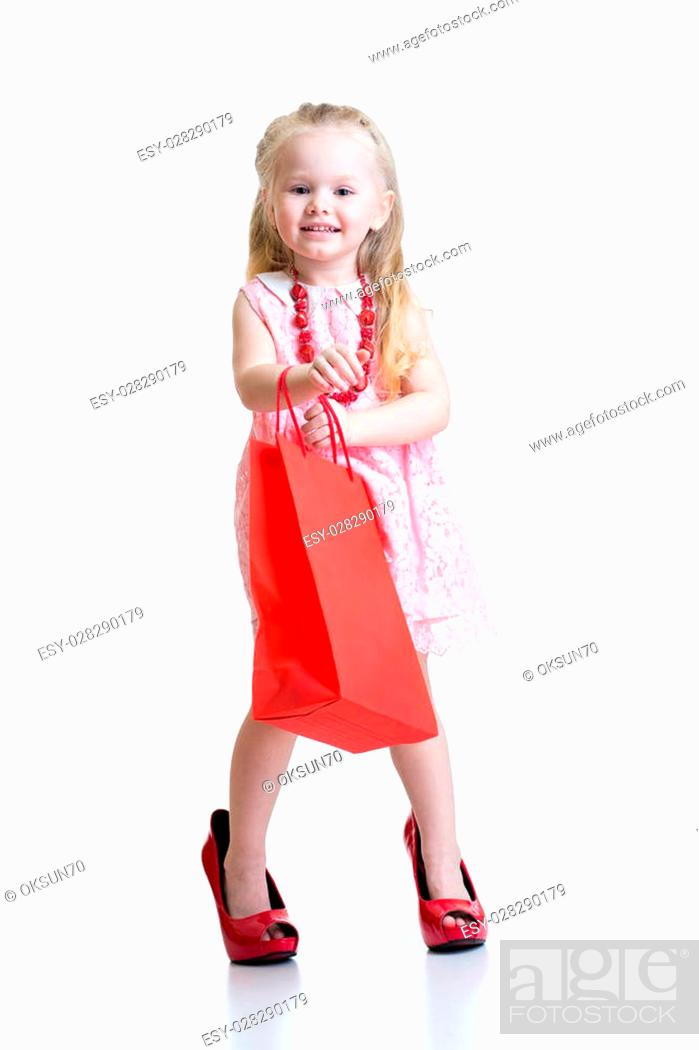 Imagen: little girl in mother shoes isolated on a white background.