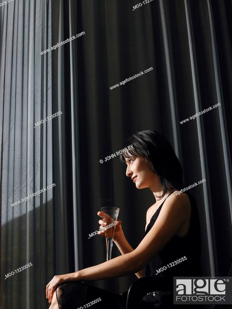 Stock Photo: Woman holding champagne in front of curtains indoors side view.