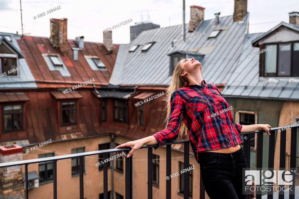 Stock Photo: Smiling young woman standing on balcony looking up.