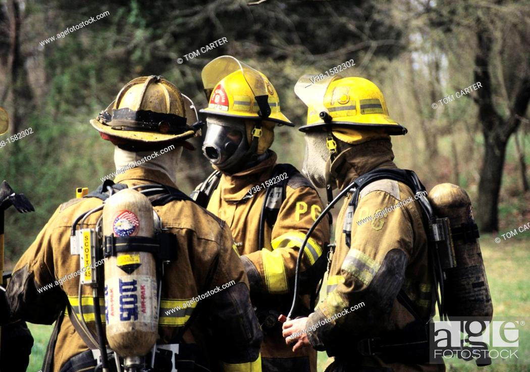 Stock Photo: Firefighters discussing strategy at a house fire.