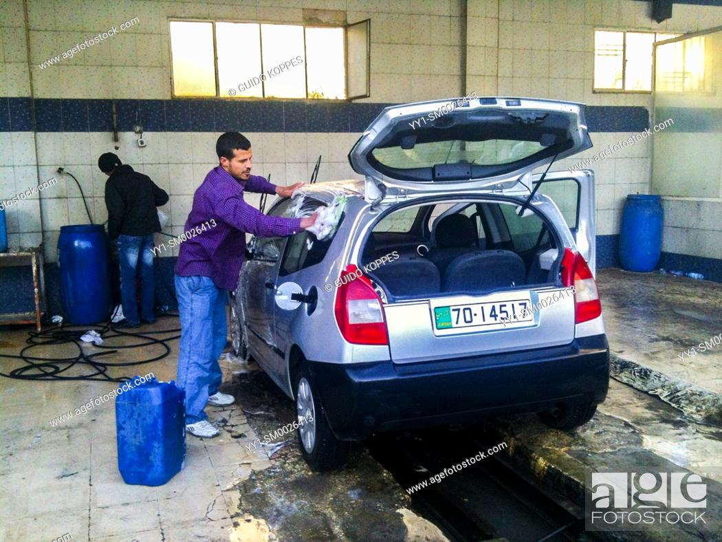 Imagen: Amman, Jordan, Young adult male washing up a rental car, after driving two weeks in the dessert between the capitol and a refugee camp for a documentary photo.