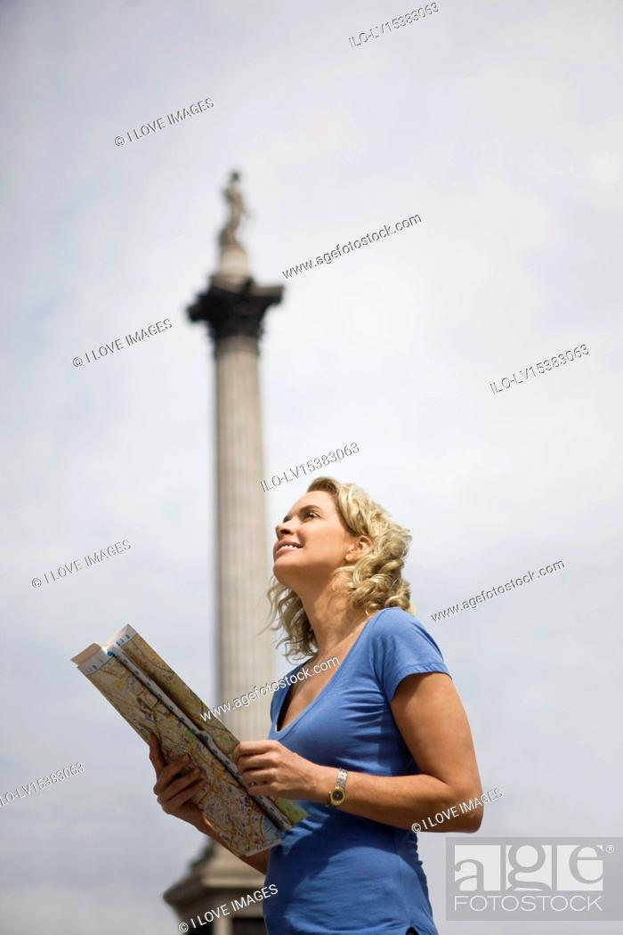 Stock Photo: A middle-aged woman standing in Trafalgar Square, looking at a map.