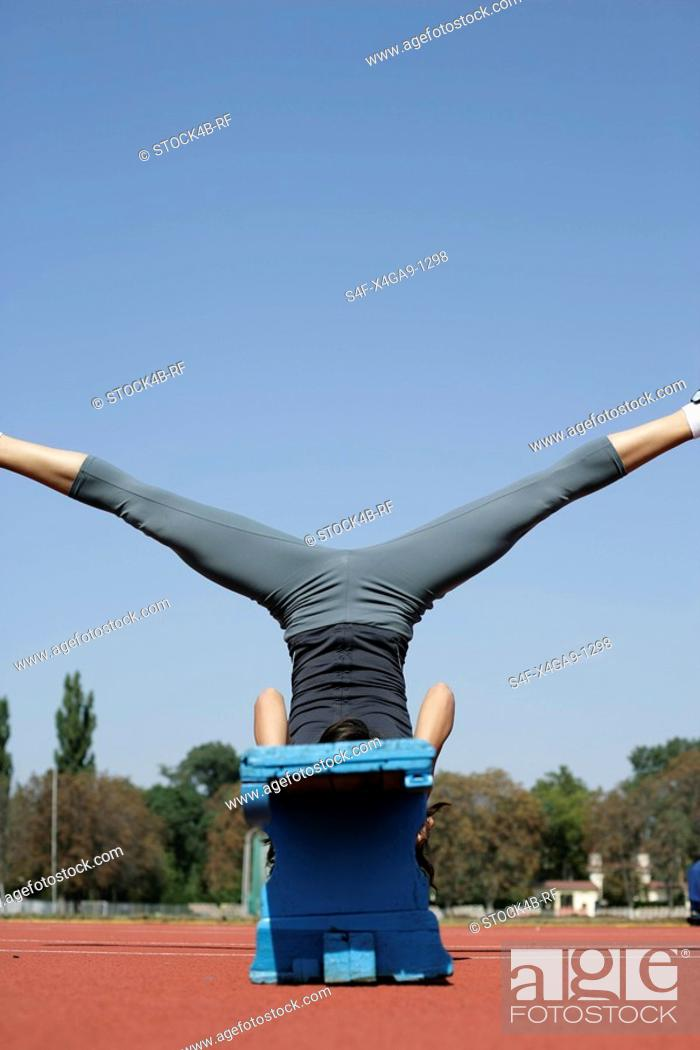 Stock Photo: Woman stretching on a bench.