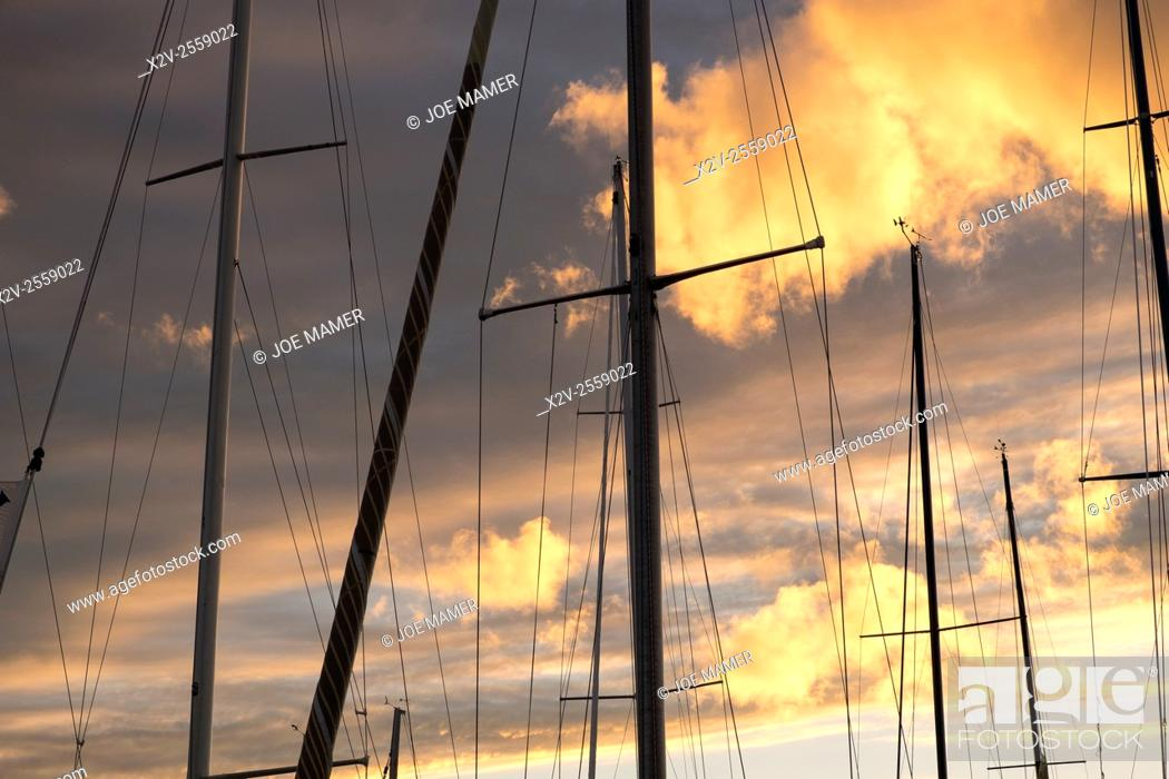 Photo de stock: Sailboat masts silhouetted against sunset.